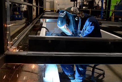 man welding metal beam